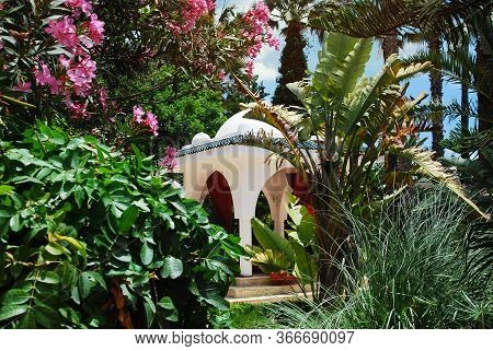 White Arbor For Relaxation In Oriental Style In Dense Thickets Of Tropical Flowering Plants