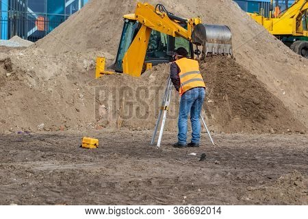 A Craftsman Is Standing At A Construction Site Near Surveying Equipment. A Special Device For Survey