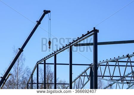 Truck Mounted Crane With A Telescoping Boom At Constructing A Metal Carcas Of A New Building