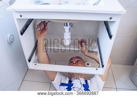 Plumber In Work Clothes Is Repairing Or Installing A Bathroom Sink