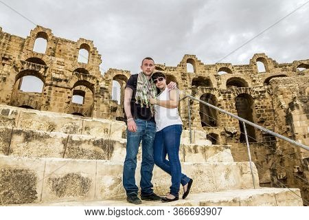 El Jam.tunisia.may 21, 2013.a Couple Of Tourists In Love Pose Against The Backdrop Of The Roman Amph