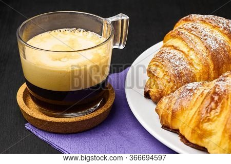 Close Up A Cup Of Espresso And Fresh Croissants On A Purple Serviette. Concept Of Breakfast On A Bla