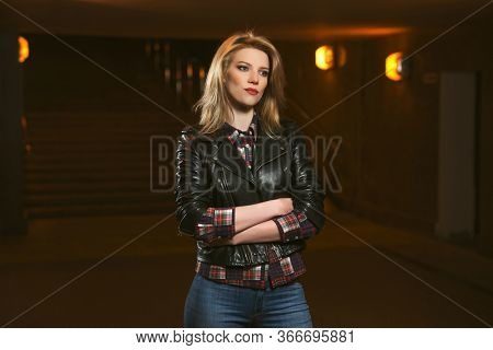 Young fashion blonde woman walking on city street at night Stylish female model in black leather jacket and dark blue jeans