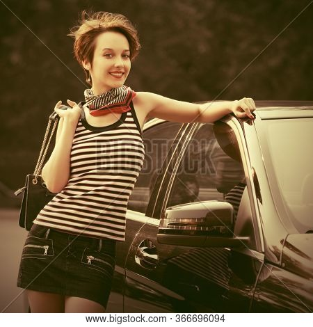 Happy young fashion woman with handbag leaning on her car Stylish female model with pixie hair in striped tank top and denim skirt