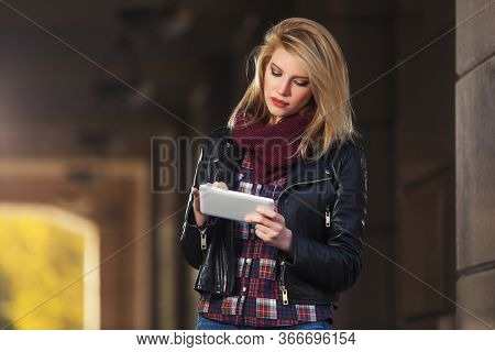 Young fashion woman using digital tablet computer on city street Stylish female model in black leather jacket and snood scarf