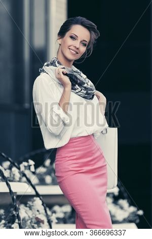 Happy young fashion business woman at office building on city street Stylish female model in white shirt and pink pencil skirt