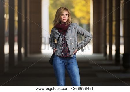Young fashion blonde woman with handbag walking on city street  Stylish female model in checked plaid blazer and snood scarf