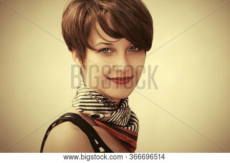 Happy young fashion woman with pixie hair on city street Stylish female model in striped tank top and silk scarf