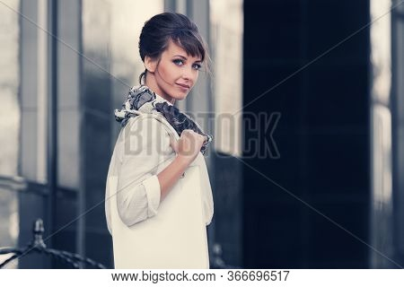 Happy young fashion business woman with handbag on city street Stylish female model in white shirt and scarf