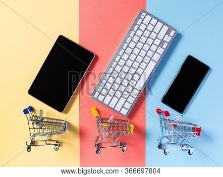 Online Shopping Concept With Supermarket Shopping Trolley Cart, Mobile Phone, Tablet And Keyboard On