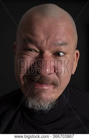 Portrait Of A Mixed Race Man With A Beard And A Disbelief Expression, On Black Background