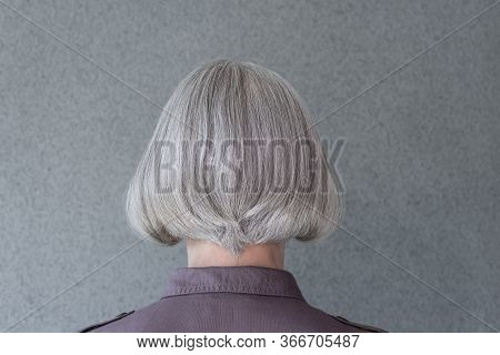 Silver-haired Mature Lady On Gray Background, From Behind.