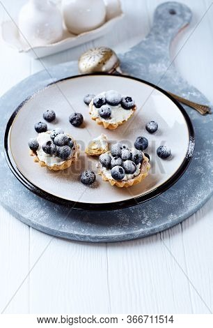 Little Mascarpone Tart With Fresh Bilberries On Bright Wooden Background.