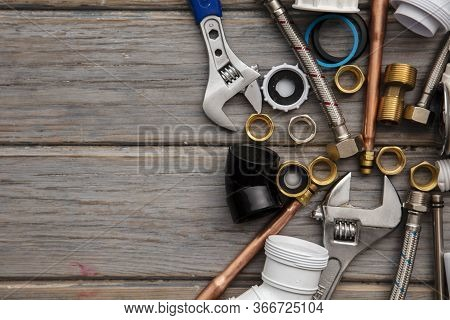 Plumbing Tools, Pipe And Fixings On A Rustic Wooden Background. Home Improvement