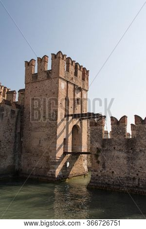 Italy, Lombardy - August 05 2018: The View Of The Walls And Bridge Across Water Moat At The Scaliger