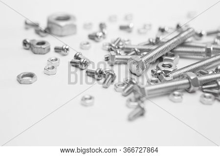 Selective Focus Of Many Nuts And Bolts On White Background