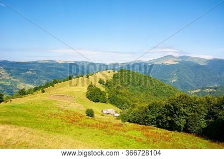 Mountain Landscape With Green Meadow On The Hill. Fluffy Clouds On The Blue Sky Above The Distant Ri