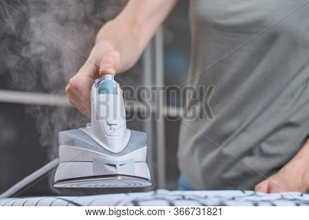 Steam Boost On The Modern Iron. Woman Ironing Clothes With Modern Iron