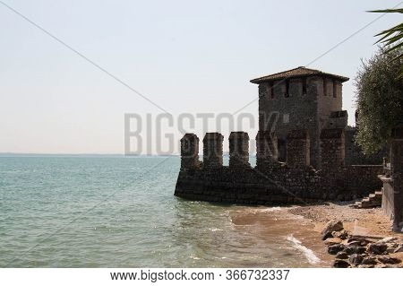 Italy, Lombardy - August 05 2018: The View Of Scaliger Castle Fortified Walls On The Edge Of Lake Ga