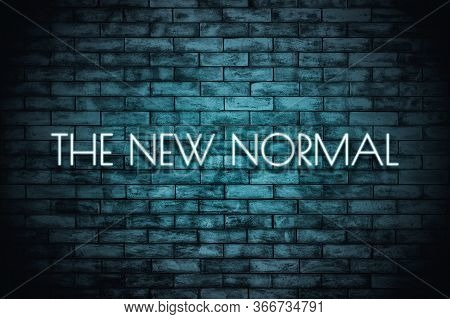 The New Normal. Neon Light Lettering  On Brickwall Background. New Normal After Covid-19 Pandemic Ba