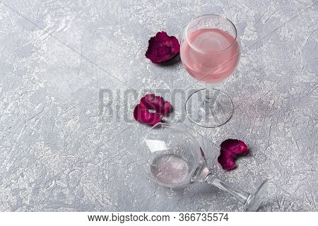 Two Glasses With Rose Wine And Red Rose Petals On A Grey Background. Half Empty Glass Lies On Its Si