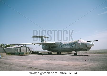Abandoned Military Aircraft On An Empty Airfield Near The Hangar Against The Blue Sky. Broken Plane