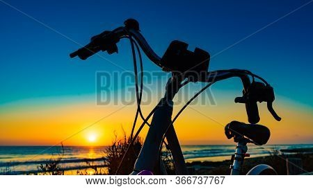 Bicycle Outdoor Parked On Beach, Evening Time, Sunset Sky. Holidays, Sport And Recreation.
