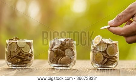 Coin In Clear Jar And Piggy Bank (home Model) On Green Nature Blur Background. Money Savings For Hom