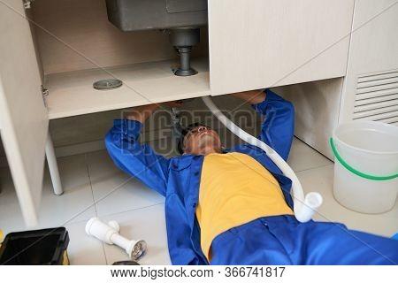 Professional Plumber Repairing Sink Pipe Leakage In Kitchen Of Customer