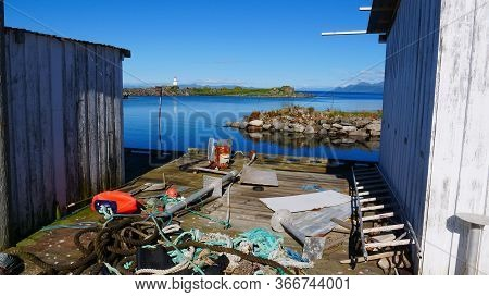 Old Port Fishing Equipment On Pier At Hovsund Village. Seascape With Lighthouse In The Background. G