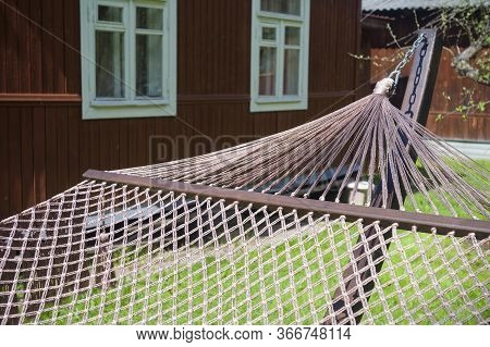A Hammock Placed On Sunlight, A Summerhouse In The Background