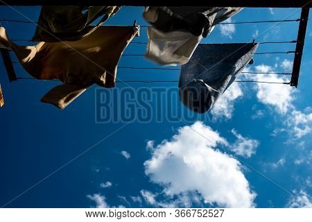Clothes Are Dried On The Wind On Background Blue Sky With Clouds. T-shirts Hanging On A Clothesline