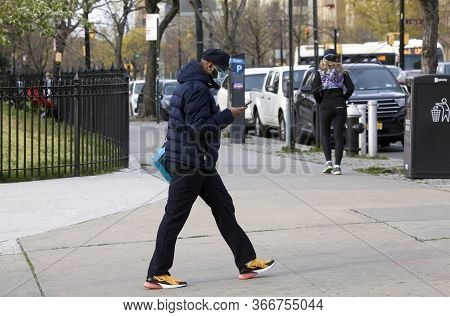 Bronx, New York/usa - April 20, 2020: Man Looks At Phone While Wearing Face Mask Outdoors During Cov