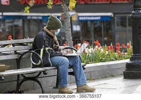 Bronx, New York/usa - April 20, 2020: Man Wearing Mask Does Work On His Laptop Outdoors During Coron