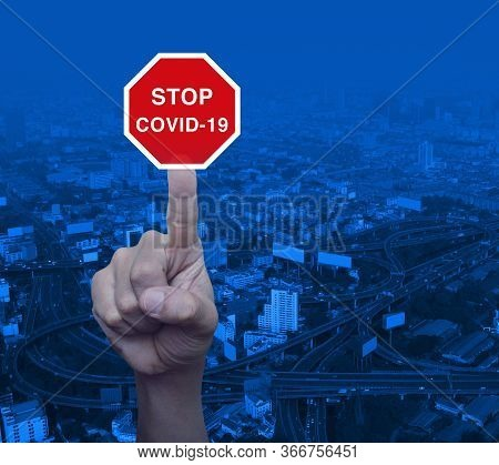 Hand Pressing Stop Covid-19 Outbreak Flat Icon Over Modern City Tower, Street, Expressway And Skyscr