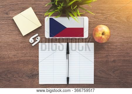 Smartphone With Czech Flag, Wireless Headphones, Notepad On A Brown Wooden Table, Concept Of Learnin