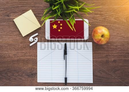 Learning Chinese, A Smartphone With A Chinese Flag And A Notebook For Writing Foreign Words On A Woo