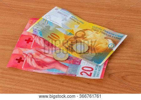 4 Polish Zlote On 10 And 20 Chf Swiss Franc Banknotes In Hand.
