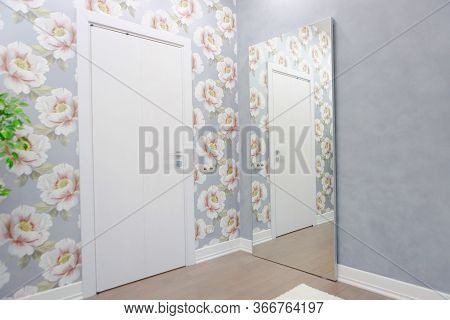Corner Of A Room With A Door And A Large Mirror On The Wall. Wall Paper Of Flowers, Gray Color Snten