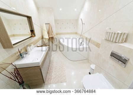 White Bathroom With Gold Trim. Corner Bathroom, Chic Mirror With Washbasin. Lamps Trimmed With Gold.