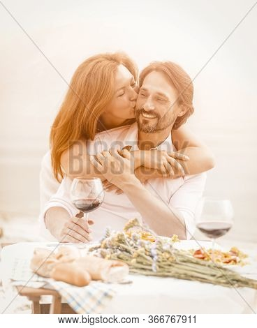 Happy Middle-aged Couple Resting In A Beach Cafe, A Beautiful Woman Tenderly Kisses Her Man Hugging