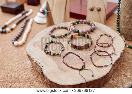 Various Handmade Gemstone Bracelets On Tree Trunk Slice