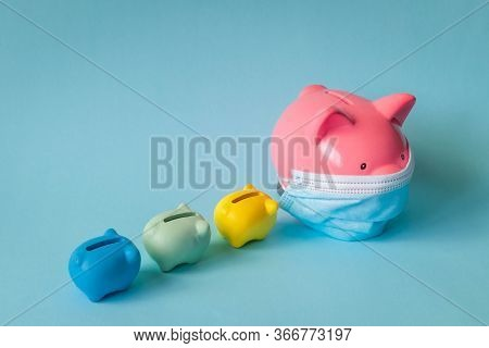 Piggy Bank With Medical Face Mask And Piglet Banks. Pink Piggy Bank Wearing Protective Mask And Foll