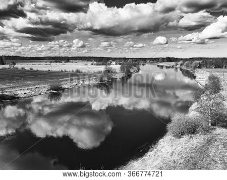 The Beautiful Clouds Reflect On The Still Water Of The River At The Rural Finland. The Spring Weathe