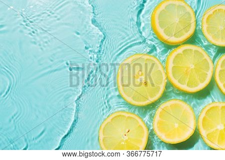 Slice Of Lemon Underwater Or In Water With Splashing And Droplet Top View Flat Lay On Blue Backgroun
