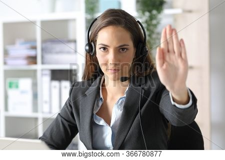 Front View Of A Serious Telemarketer Woman With Headset Gesturing Stop Sitting At The Office