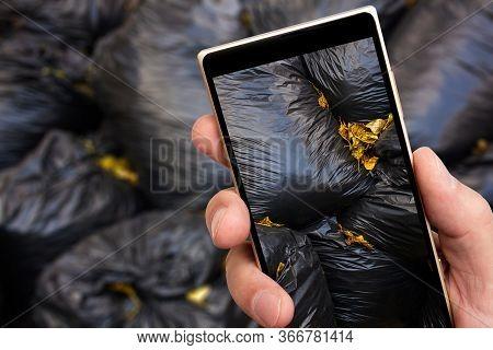 Garbage Bags On Smartphone Screen. Garbage Removal. Black Trash Bags.