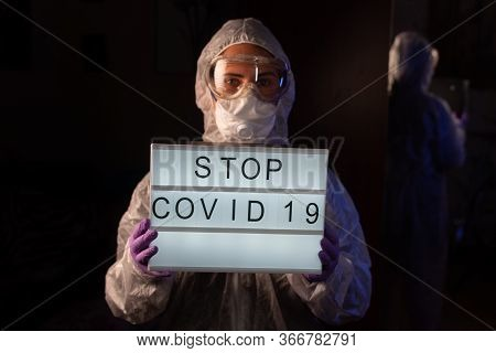 Doctor, Virologist, Scientist, Man Wearing Chemical Protection Suit, Respirator Holding Lightbox Wit