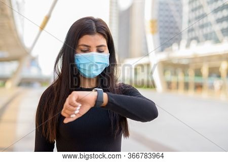 Young Indian Woman With Mask Checking The Time At The Skywalk Bridge