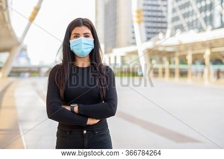 Young Indian Woman Wearing Mask With Arms Crossed At The Skywalk Bridge
